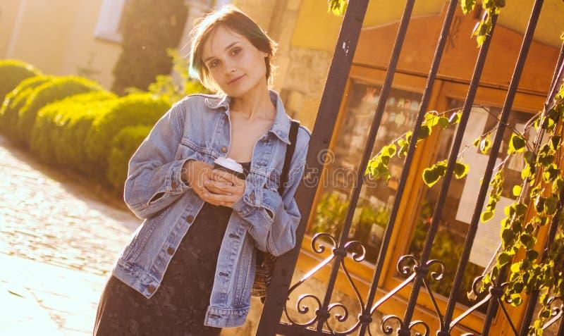 Μια γυναίκα στέκεται στις ακτίνες του ήλιου ρύθμισης με ένα φλιτζάνι του καφέ πορτρέτο πόλεων στοκ φωτογραφίες