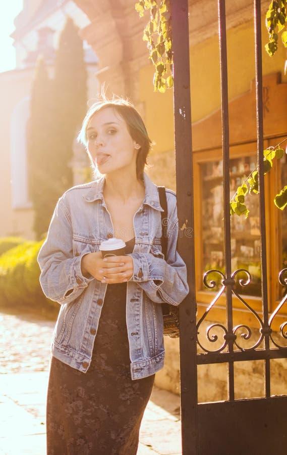 Μια γυναίκα στέκεται στις ακτίνες του ήλιου ρύθμισης με ένα φλιτζάνι του καφέ πορτρέτο πόλεων στοκ εικόνα με δικαίωμα ελεύθερης χρήσης
