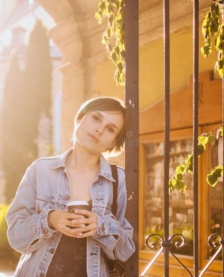 Μια γυναίκα στέκεται στις ακτίνες του ήλιου ρύθμισης με ένα φλιτζάνι του καφέ πορτρέτο πόλεων στοκ φωτογραφία με δικαίωμα ελεύθερης χρήσης