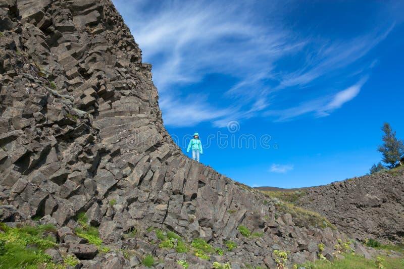 Μια γυναίκα στέκεται στον απότομο βράχο του καταρράκτη Hjalparfoss στην Ισλανδία στοκ εικόνα