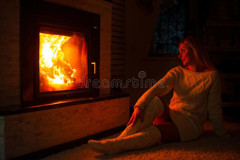 Μια γυναίκα στις πλεκτές κάλτσες κάθεται κοντά στην εστία σε ένα κρύο χειμερινό βράδυ στοκ φωτογραφίες