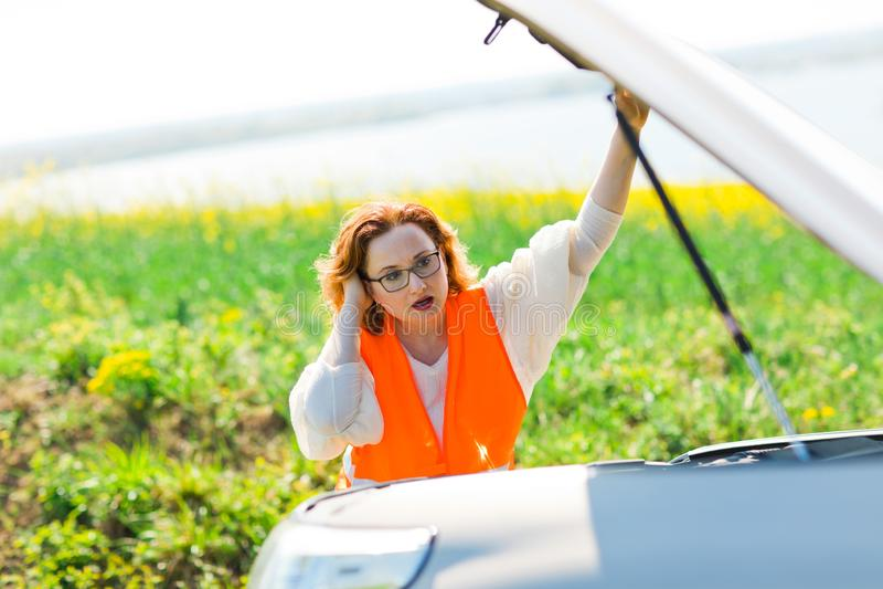 Μια γυναίκα στο πορτοκαλί καπό αυτοκινήτων φανέλλων ανοικτό του σπασμένου αυτοκινήτου στοκ εικόνα με δικαίωμα ελεύθερης χρήσης