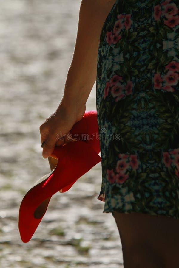 Μια γυναίκα στο πράσινο φόρεμα κρατά ένα ζευγάρι των κόκκινων υψηλών τακουνιών στο χέρι της στοκ εικόνες