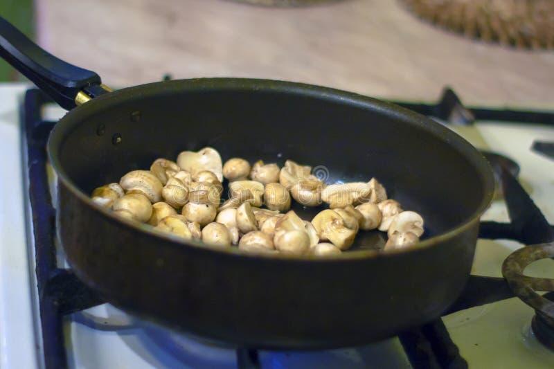 Μια γυναίκα τηγανίζει τα μανιτάρια στην κουζίνα Η διαδικασία σε ένα τηγανίζοντας τηγάνι Προετοιμασία των τροφίμων από τη συνταγή  στοκ εικόνες