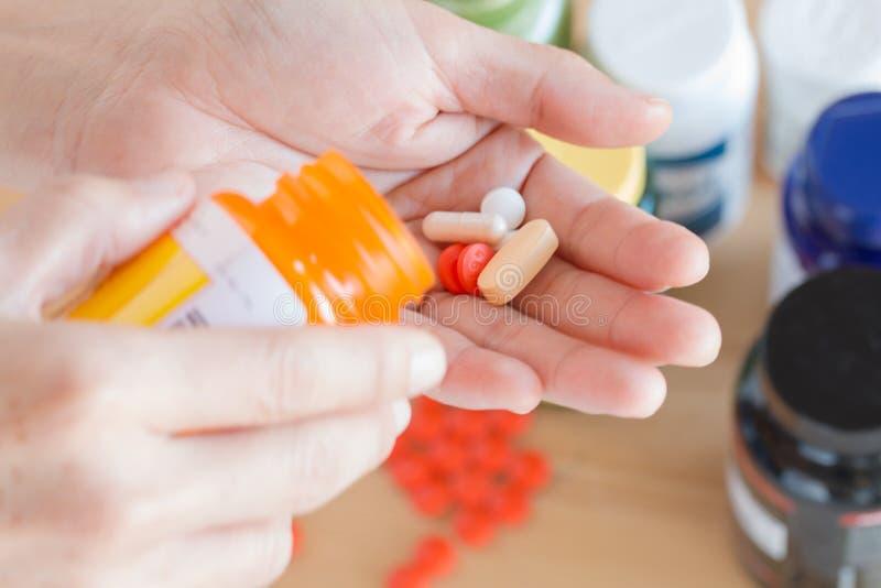 Μια γυναίκα χύνει τα χάπια, τη βιταμίνη και το συμπλήρωμα από το μπουκάλι στο χέρι στοκ φωτογραφία