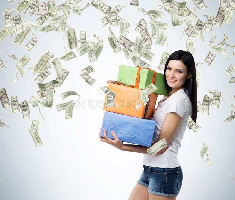 Μια γυναίκα brunette κρατά τρία ζωηρόχρωμα κιβώτια δώρων στοκ εικόνες με δικαίωμα ελεύθερης χρήσης