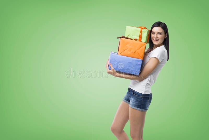 Μια γυναίκα brunette κρατά τρία ζωηρόχρωμα κιβώτια δώρων στοκ εικόνες