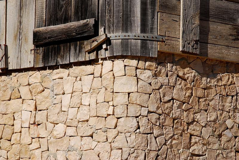 Μια γωνία τακτοποίησε υπό μορφή φραγμών πετρών και ξύλινου μέρους του φράκτη στοκ εικόνες