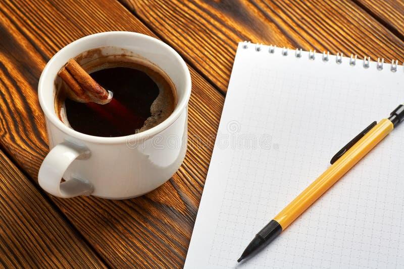 Μια δέσμη της κανέλας έπλεξε με ένα σχοινί, ένα φλιτζάνι του καφέ και ένα σημειωματάριο για το γράψιμο σε μια ξύλινη κινηματογράφ στοκ φωτογραφία