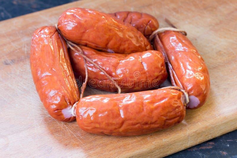Μια δέσμη των ορεκτικών σπιτικών λουκάνικων κρέατος σε έναν τέμνοντα πίνακα στοκ φωτογραφία με δικαίωμα ελεύθερης χρήσης