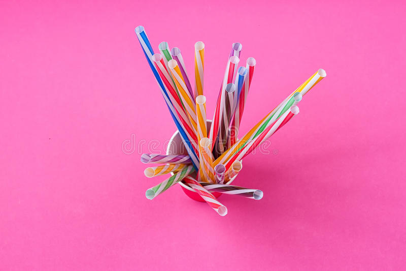 Μια δέσμη των πολύχρωμων αχύρων κατανάλωσης σε ένα φλυτζάνι εγγράφου στοκ φωτογραφία