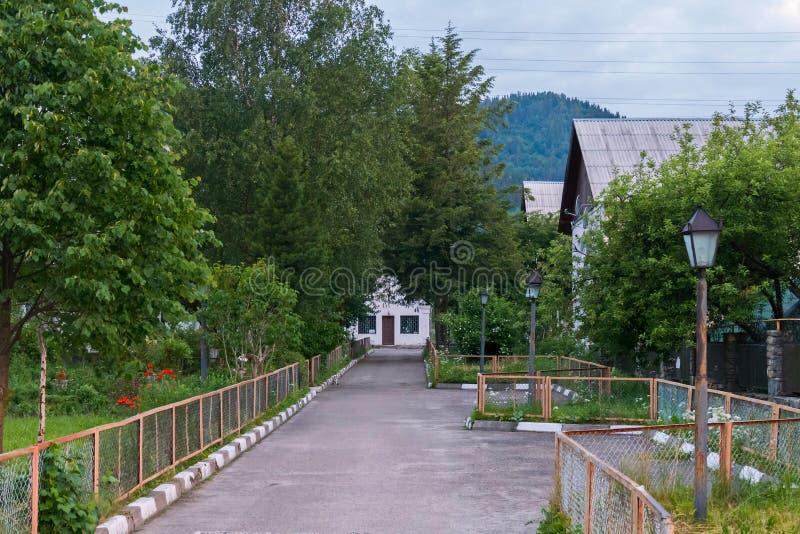 Μια διαδρομή ασφάλτου με το λευκό Μαύρο συγκρατεί το τρέξιμο κατά μήκος των σπιτιών και ενός πράσινου χορτοτάπητα με τα δέντρα πο στοκ φωτογραφίες με δικαίωμα ελεύθερης χρήσης