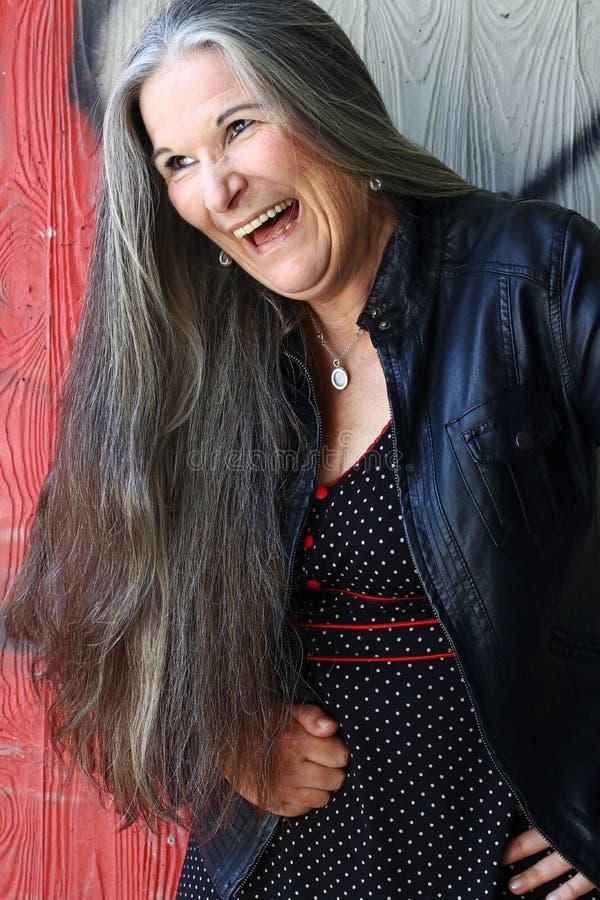 Μια δυνατά γελώντας ηλικιωμένη γυναίκα με τη μακριά γκρίζα τρίχα στοκ φωτογραφία με δικαίωμα ελεύθερης χρήσης