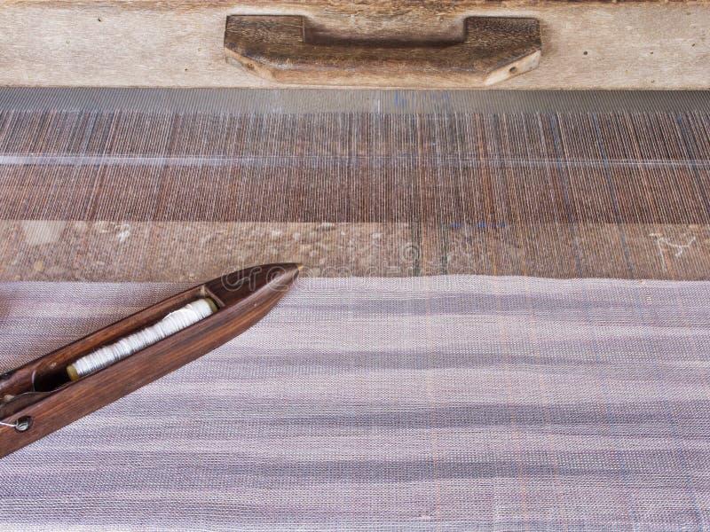 Μια εικόνα κινηματογραφήσεων σε πρώτο πλάνο μιας παλαιάς ξύλινης σαΐτας στα σπιτικά νήματα και τον υφαίνοντας αργαλειό, παραδοσια στοκ εικόνες