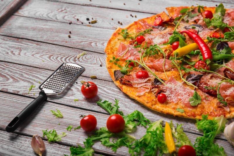 Μια εικόνα κινηματογραφήσεων σε πρώτο πλάνο της φρέσκιας pepperoni πίτσας σε ένα αγροτικό επιτραπέζιο υπόβαθρο Ολόκληρη ιταλική π στοκ φωτογραφίες