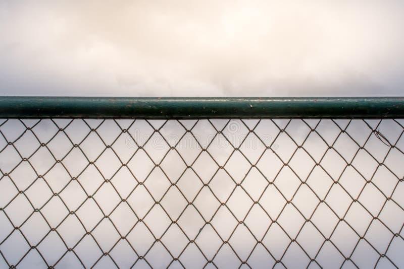 Μια εικόνα κινηματογραφήσεων σε πρώτο πλάνο του σκουριασμένου παλαιού φράκτη συνδέσεων αλυσίδων με ένα σαφές υπόβαθρο ουρανού κατ στοκ εικόνα με δικαίωμα ελεύθερης χρήσης