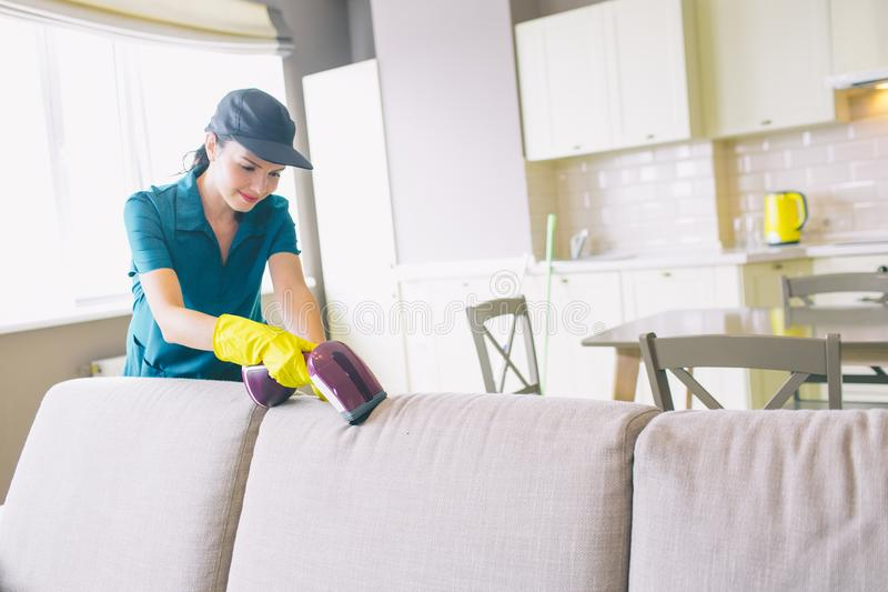 Μια εικόνα της καθαρίζοντας άκρης κοριτσιών του καναπέ Χρησιμοποιεί τη μικρή ηλεκτρική σκούπα Η γυναίκα είναι επαγγελματική Εργάζ στοκ εικόνες