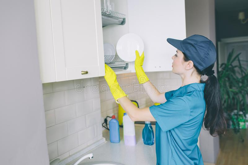 Μια εικόνα του καθαριστή που βάζει το πιάτο στο ντουλάπι Το ανοίγουν Το κορίτσι φορά τα μπλε ομοιόμορφα και κίτρινα γάντια Καθαρί στοκ εικόνες