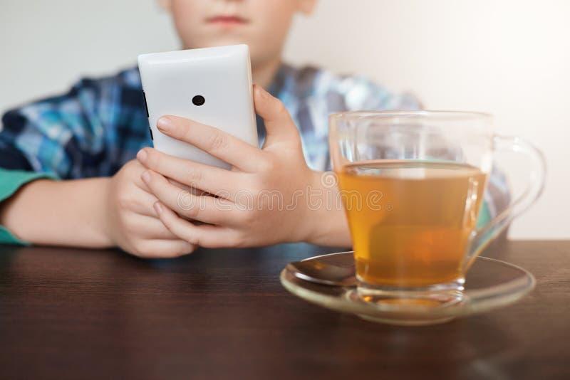 Μια εικόνα του μικρού παιδιού έντυσε το ελεγχμένο πουκάμισο που εγκαθιστά στον πίνακα με ένα φλυτζάνι του smartphone εκμετάλλευση στοκ εικόνες