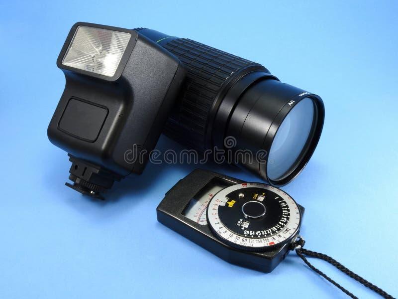 Μια εκλεκτής ποιότητας λάμψη καμερών φωτογραφιών, ένας φακός καμερών ζουμ και ένα φωτόμετρο στοκ εικόνα