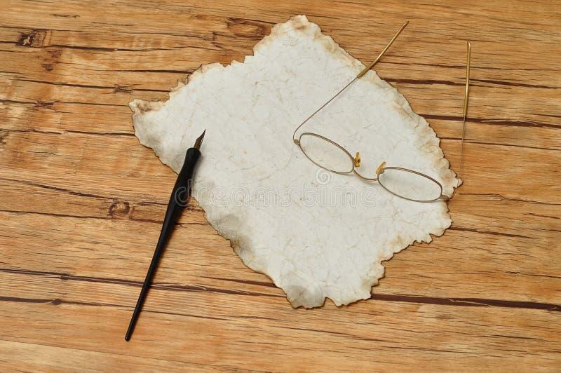Μια εκλεκτής ποιότητας μαύρη μάνδρα πηγών με το παλαιά έγγραφο και τα γυαλιά στοκ εικόνες