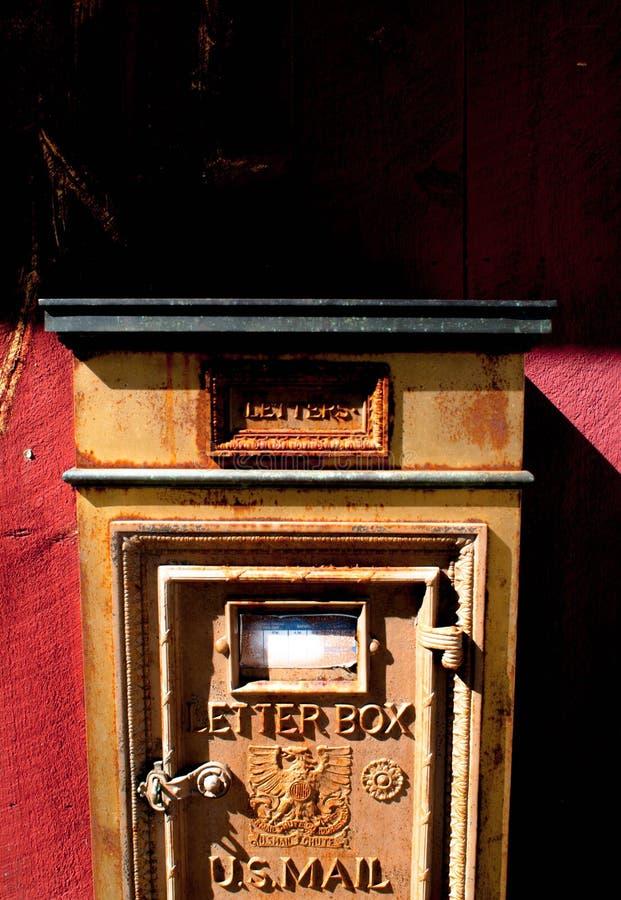 Μια εκλεκτής ποιότητας ταχυδρομική θυρίδα σε έναν κόκκινο τοίχο στοκ φωτογραφία