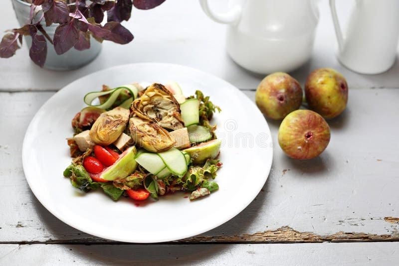 Μια ελαφριά χορτοφάγος σαλάτα με το σύκο, αγκινάρα, αγγούρι, ντομάτες, φέτα στα φύλλα ruccola, που ολοκληρώνονται με τη σάλτσα σμ στοκ φωτογραφίες