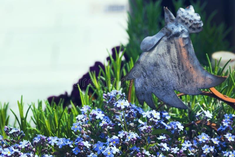Μια ενδιαφέρουσα λεπτομέρεια είναι ένας κόκκορας μετάλλων μεταξύ των λουλουδιών Τα μικρά μπλε λουλούδια αυξάνονται στον κήπο μια  στοκ εικόνα