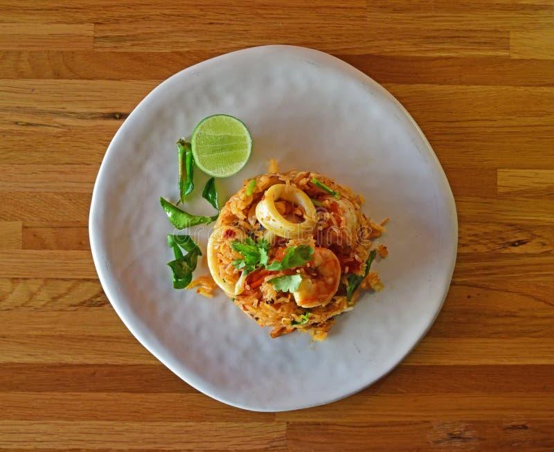 Μια εξυπηρέτηση των εύγευστων θαλασσινών Tom Yum τηγάνισε το ρύζι σε ένα στρογγυλό άσπρο πιάτο στοκ εικόνες