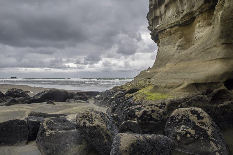 Μια επιβολή ξεπέρασε τον απότομο βράχο σε μια παραλία στοκ φωτογραφίες