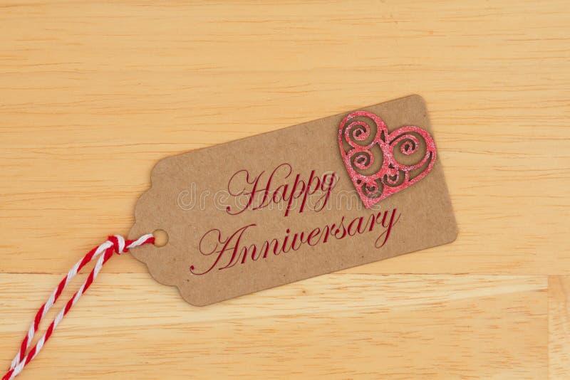 Μια ετικέττα δώρων στο ξύλο με μια καρδιά με την ευτυχή επέτειο κειμένων στοκ φωτογραφίες με δικαίωμα ελεύθερης χρήσης