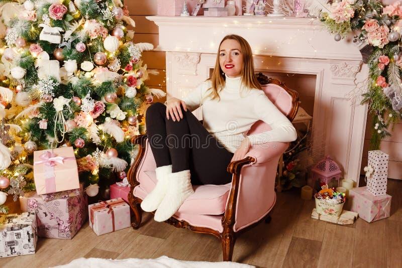 Μια ευτυχής γυναίκα με τα κόκκινα χείλια σε ένα μπεζ πουλόβερ και τις παντόφλες κάθεται σε μια ρόδινη καρέκλα στο δωμάτιο Χριστου στοκ φωτογραφία με δικαίωμα ελεύθερης χρήσης