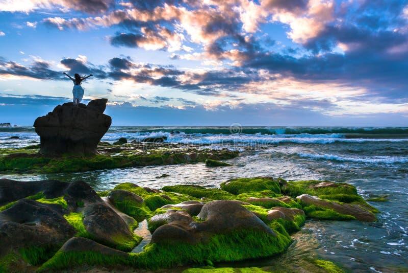 Μια ευτυχής γυναίκα στέκεται πάνω από το λίθο στην παραλία και απολαμβάνει της ελευθερίας στην ανατολή στοκ εικόνα