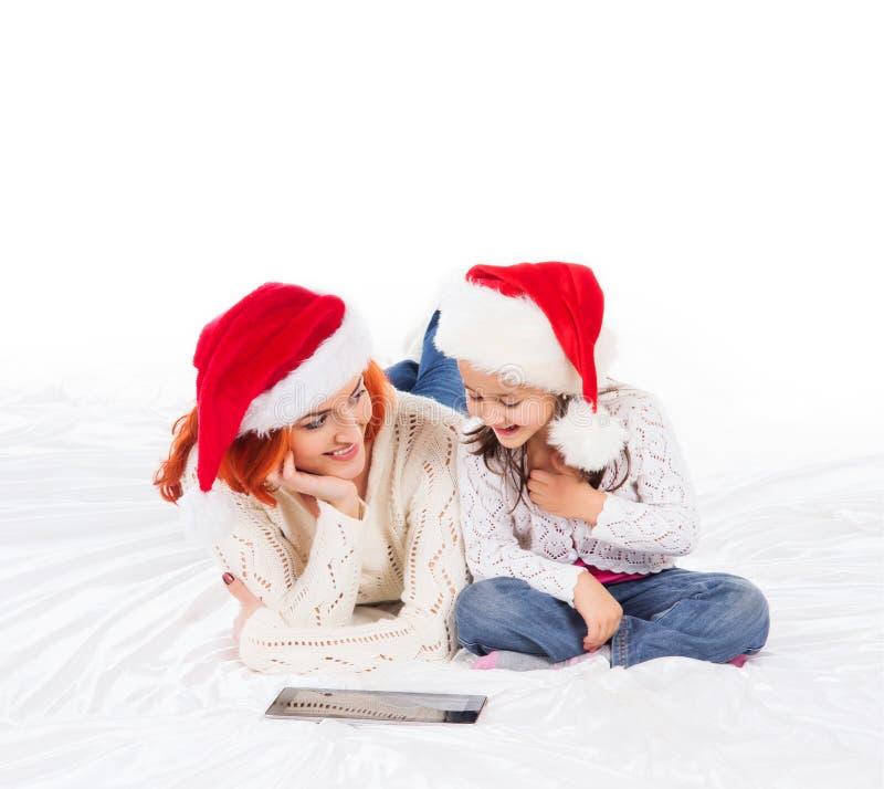 Μια ευτυχής μητέρα και μια κόρη στα καπέλα Χριστουγέννων στοκ εικόνα με δικαίωμα ελεύθερης χρήσης
