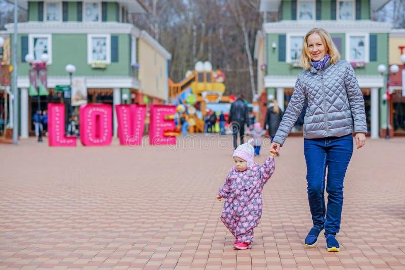 Μια ευτυχής νέα μητέρα περπατά πέρα από το τετράγωνο από το χέρι με την λίγη κόρη Τα πρόσωπα καίγονται με την ευτυχία στοκ εικόνα με δικαίωμα ελεύθερης χρήσης