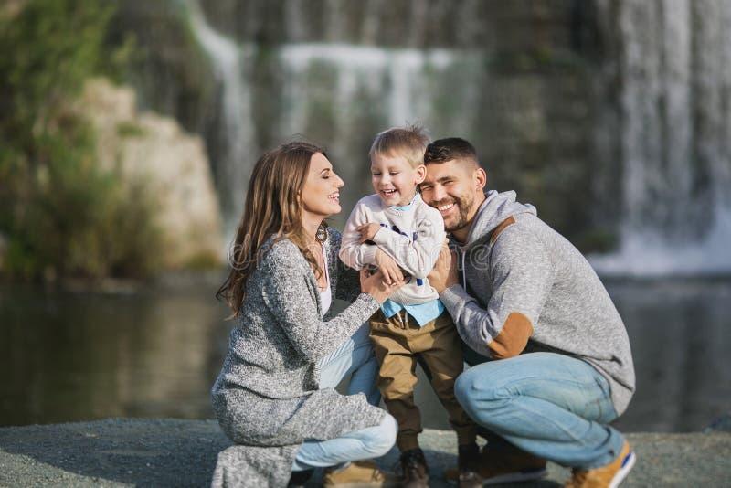 Μια ευτυχής νέα οικογένεια σε ένα υπόβαθρο καταρρακτών στοκ φωτογραφίες με δικαίωμα ελεύθερης χρήσης
