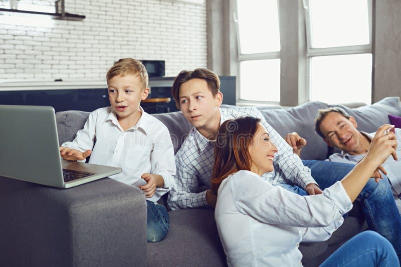 Μια ευτυχής οικογένεια με ένα lap-top έχει τη διασκέδαση στοκ φωτογραφίες