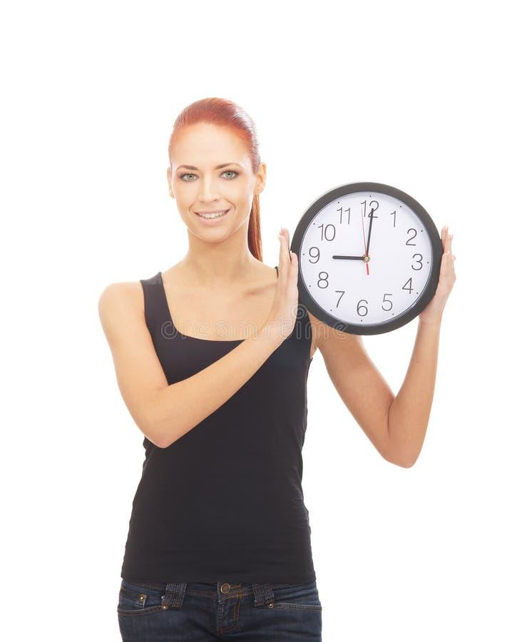 Μια ευτυχής redhead γυναίκα που κρατά ένα μεγάλο ρολόι στοκ φωτογραφία με δικαίωμα ελεύθερης χρήσης