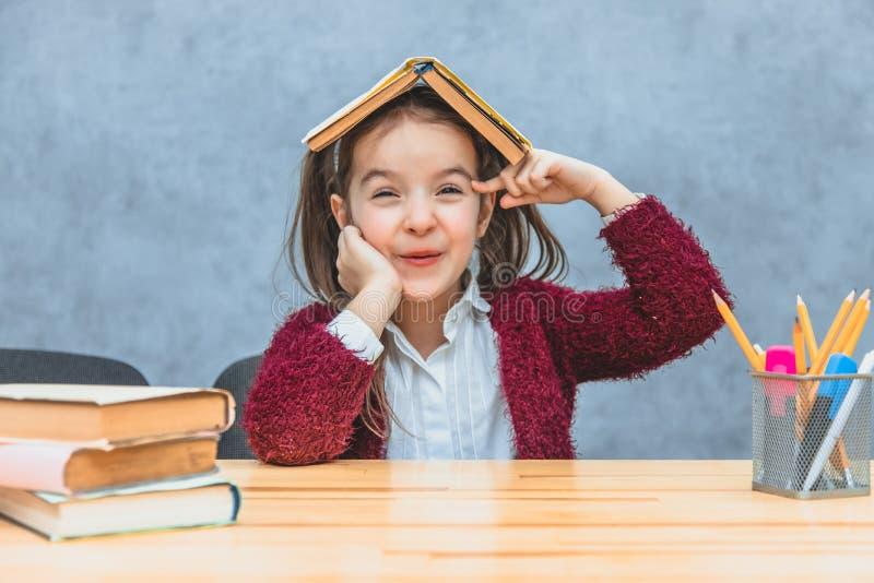 Μια εύθυμες συνεδρίαση και μια εκμετάλλευση κοριτσιών ένα βιβλίο πέρα από το κεφάλι της πέρα από ένα γκρίζο υπόβαθρο Κατά τη διάρ στοκ φωτογραφία με δικαίωμα ελεύθερης χρήσης