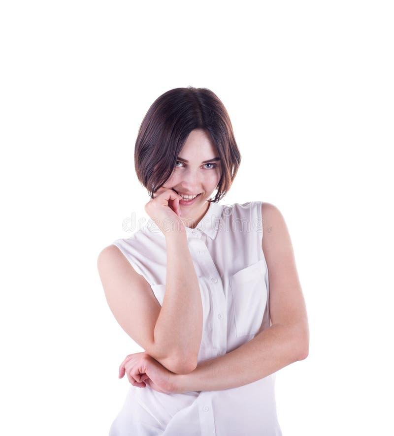 Μια εύθυμη γυναίκα Μια κυρία brunette που απομονώνεται σε ένα άσπρο υπόβαθρο Ένα περίεργο κορίτσι που δαγκώνει το δάχτυλό της Ένα στοκ εικόνα με δικαίωμα ελεύθερης χρήσης