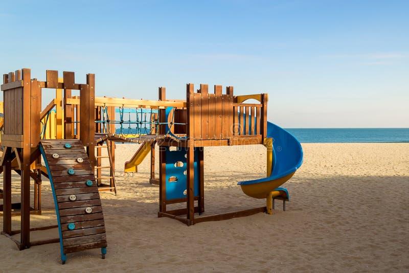 Μια ζωηρόχρωμη παιδική χαρά παιδιών σε μια κενή αμμώδη παραλία θάλασσας Θερμός χειμώνας χωρίς χιόνι, χειμερινή παραλία χωρίς ανθρ στοκ εικόνες με δικαίωμα ελεύθερης χρήσης
