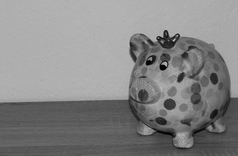 Μια ζωηρόχρωμη piggy τράπεζα σε γραπτό που απομονώνεται σε ένα ξύλινο υπόγειο και άσπρο υπόβαθρο στοκ εικόνες με δικαίωμα ελεύθερης χρήσης