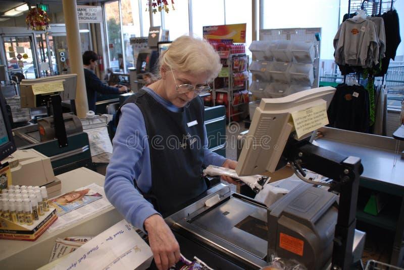 Μια ηλικιωμένη γυναίκα εργάζεται ως ταμίας σε ένα μανάβικο σε Greenbelt, Μέρυλαντ στοκ φωτογραφία