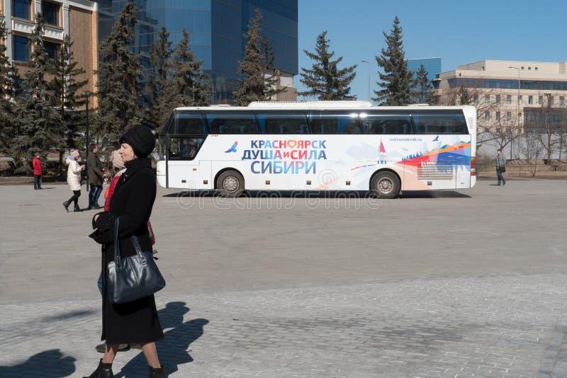Μια ηλικιωμένη γυναίκα περιμένει ένα τουριστηκό λεωφορείο δύο-ιστορίας στοκ εικόνες με δικαίωμα ελεύθερης χρήσης