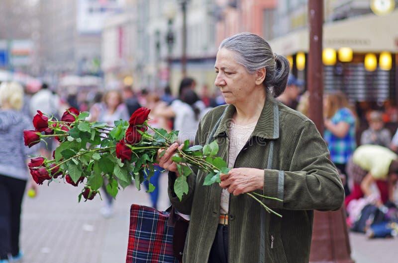 Μια ηλικιωμένη γυναίκα συλλέγει μια ανθοδέσμη από τα κόκκινα τριαντάφ στοκ εικόνες με δικαίωμα ελεύθερης χρήσης