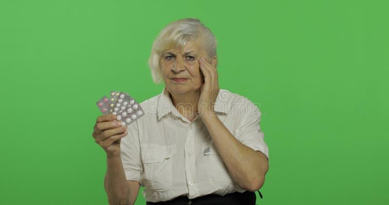 Μια ηλικιωμένη δυσαρεστημένη εξέταση γυναικών τα χάπια φουσκαλών E στοκ εικόνες