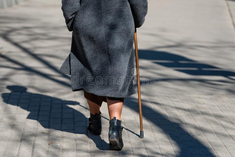 Μια ηλιόλουστη ημέρα μια ηλικιωμένη γυναίκα που περπατά κάτω από την οδό με το περπάτημα στοκ φωτογραφία με δικαίωμα ελεύθερης χρήσης
