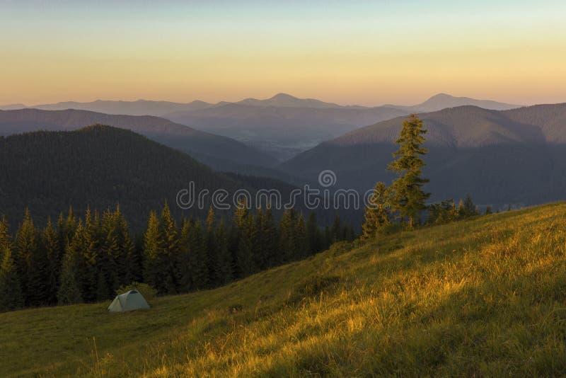μια ηλιόλουστη θερινή ημέρα, την άποψη από το οροπέδιο στο δάσος και τα βουνά Μπλε ουρανός, μέρη της πράσινης χλόης και δέντρα στοκ φωτογραφίες