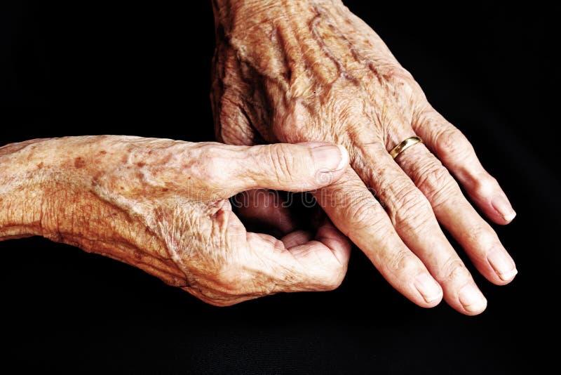 Μια ηλικιωμένη γυναίκα έχει τον πόνο στα χέρια του στοκ εικόνες