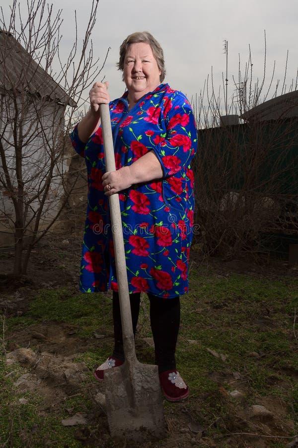 Μια ηλικιωμένη γυναίκα με ένα φτυάρι στοκ φωτογραφία με δικαίωμα ελεύθερης χρήσης